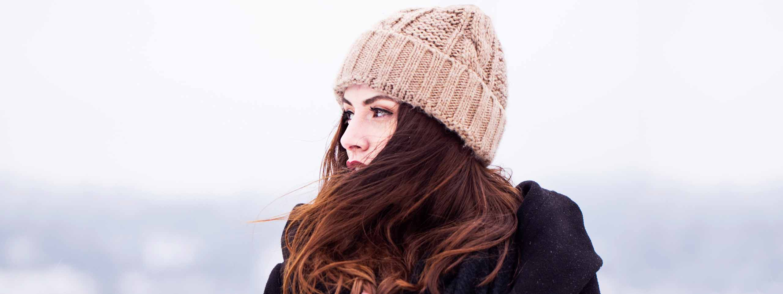 Woman with brown hair and hat in winter