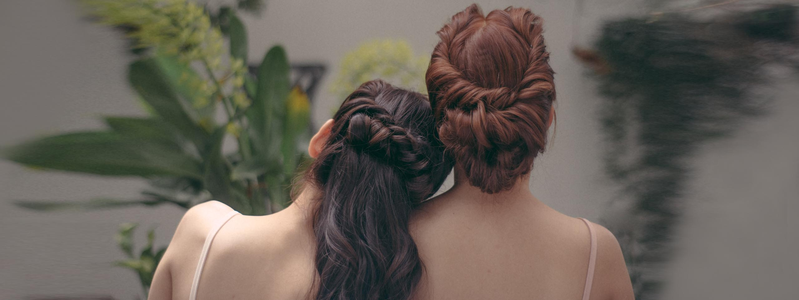 Two women with wedding hair stand with their backs to the camera: One with long, dark, curly hair, and the other with a reddish-brown updo